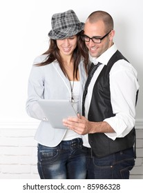 Trendy couple leaning on wall with electronic tablet
