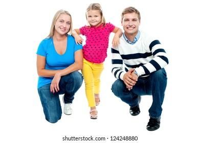 Trendy couple squatting with girl child in between. Studio shot