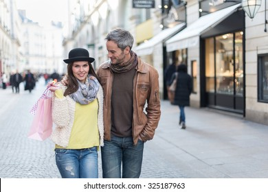 A trendy couple is walking arm in arm in the city center. They are in a cobbled car-free street. The woman is wearing a black hat and a pink shopping bag and the grey hair man has a leather coat