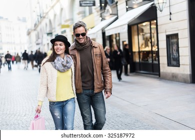 A trendy couple is walking in the city center. They are in a cobbled car-free street. The woman is wearing a black hat and a pink shopping bag and the man has sunglasses and a leather coat