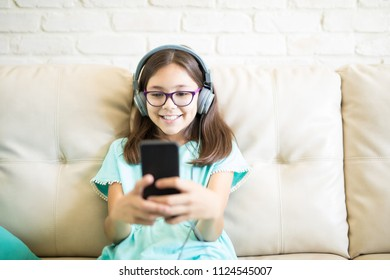 Trendy cute girl relaxing at home listening to music in headphones