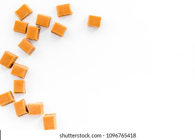 Trendy dessert. Salted caramel. Caramel cubes sprinkled by salt crystals on white background top view space for text