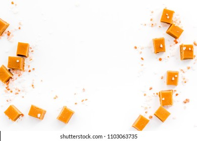 Trendy dessert. Salted caramel. Caramel cubes sprinkled by salt crystals on white background top view.