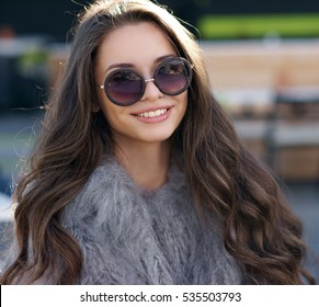 Trendy dressed fashionable girl wearing fur coat. Young pretty beautiful woman with long curly hair looking at you.