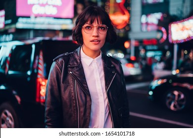 Trendy dressed hipster girl in eyewear for vision correction fascinated with metropolitan urbanity, youthful gorgeous female in leather jacket standing on city street in New York during evening
