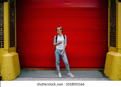 Trendy dressed hipster girl looking away holding smartphone sin smartphone while standing near publicity area, young woman posing on bright colourful copy space background with mobile phone device
