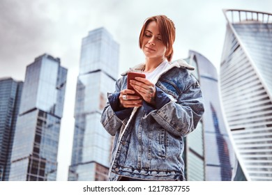 Trendy dressed hipster girl with tattoos on her face and hand using a smartphone in front of skyscrapers in Moskow city at cloudy morning.
