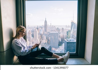Trendy dressed hipster girl using digital tablet while sitting on hotel window sill with breathtaking scenery view of downtown cityscape. Female working in office with beautiful view of downtown