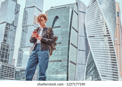 Trendy dressed redhead student girl with tattoos on her face using a smartphone in front of skyscrapers in Moskow city.