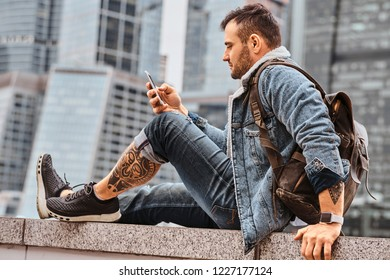 Trendy dressed tattooed hipster man with a backpack using smartphone in front of skyscrapers in Moskow city at cloudy morning.