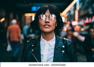 Trendgekleideter Tourist in stilvollen Brillen mit Neonreflexion, der beim Abendausflug in die Metropole aufblickt, eine modische Frau in Spektakeln, die in der Nachtstadt herumhängt