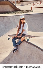 Trendy dressed young skater girl with a longboard sitting on a skatepark.
