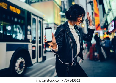Trendy dressed young woman feeling carefree dancing to favorite song listening to in earphones, happy hipster girl having fun on evening city street with neon illumination moving to sound on music