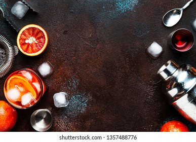Trendy drink, alcoholic cocktail Negroni with dry gin, red vermouth and red bitter, orange slice and ice cubes. Brown bar counter background, bar tools, top view, summer mood concept, copy space