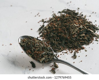 Trendy drink idea: Tea-Coffee Blend Combines Two Popular Drinks. Heap of dry mix of green tea and ground roasted coffee beans. Close up view. White marble tabletop.