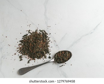 Trendy drink idea: Tea-Coffee Blend Combines Two Popular Drinks. Heap of dry mix of green tea and ground roasted coffee beans. Close up view. White marble tabletop. Top view or flat lay.