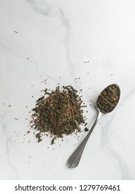 Trendy drink idea: Tea-Coffee Blend Combines Two Popular Drinks. Heap of dry mix of green tea and ground roasted coffee beans. Close up view. White marble tabletop. Top view or flat lay. Vertical.
