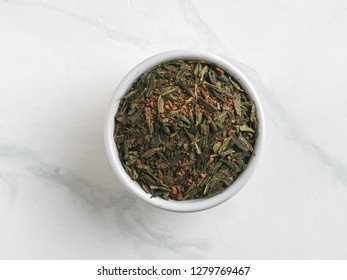 Trendy drink idea: Tea-Coffee Blend Combines Two Popular Drinks. Small bowl of dry mix of green tea and ground roasted coffee beans. Top view or flat lay. Copy space