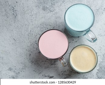 Trendy drinks: Blue, yellow and pink latte. Top view of hot butterfly pea or blue spirulina latte, yellow or gold turmeric latte and pink beetroot latte on gray cement background. Copy space for text