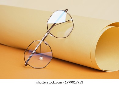 trendy eye glasses on rolled beige paper, geometric background, trending colors, yellow background copy space