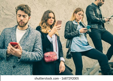 Trendy, fashion friends, using smartphones in the street disposed on a staircase.  Technology concept of millennial generation people using social media and the internet everywhere. Urban shot.