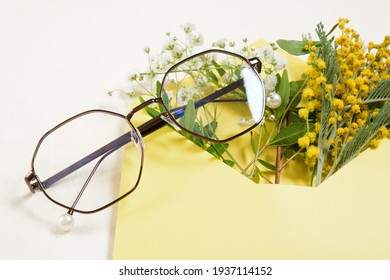 trendy fashion modern glasses and a bouquet of spring flowers in an envelope on a beige light background copy space, summer and spring mood concept