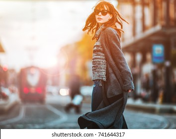 Trendy fashion woman in coat walking on the street, urban city scene
