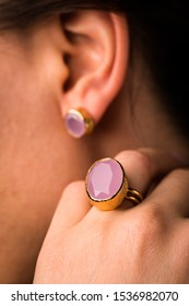 Trendy fashionable earrings and ring with pink oval sapphire and golden metal on white isolated background, copy space, pink gem stone