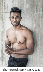 Trendy and fashionable young arab male model with a muscled gym fit body and a trendy haircut is posing nude and shirtless in front of a grey concrete wall