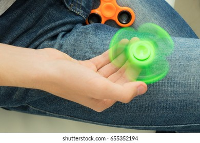 trendy fidget spinner - person holding spinning green fidget spinner in hand, close up view