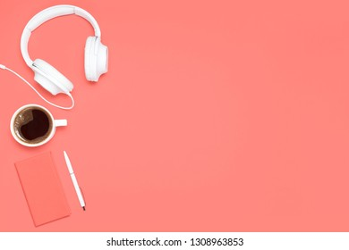 Trendy flat lay composition with colored diary, white pen, white cup of cofffee and white headphones on caral colored desk. Mockup with copy space for bloggers, designers, magazines etc.
