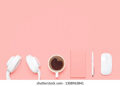 Trendy flat lay mockup with headphones, diary, pen, wireless mouse and cup of coffee on colored desk. Top view. Modern feminine workspace.