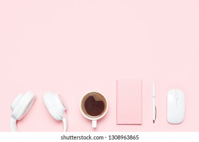 Trendy flat lay mockup with headphones, diary, pen, wireless mouse and cup of coffee on pink colored desk. Top view. Modern feminine workspace.