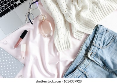Trendy flatlay of laptop, women clothes and cosmetics, accessories, notepad. Lifestyle concept