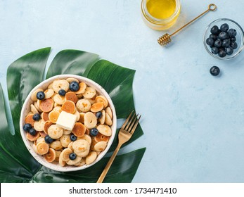 Trendy food - pancake cereal. Heap of mini cereal pancakes in boul on blue background. Copy space left for text. Top view or flat lay.