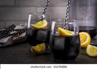 Trendy food. Summer refreshment drinks. Detox and diet concept. Black lemonade with charcoal, ice, lemon juice and lemon. On a home stone table, with black straws for drinking. Copy space.