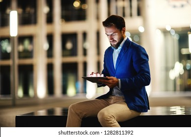 Trendy formal man in suit sitting against illuminated building in night time and browsing tablet