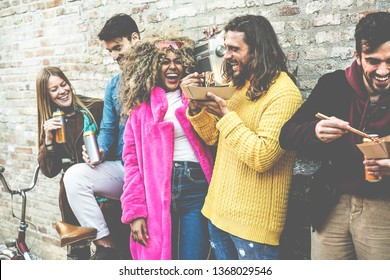Trendy friends from diverse culture eating street food outdoor - Yong trendy people having fun together drinking and laughing together - City lifestyle and party concept - Focus on center man face