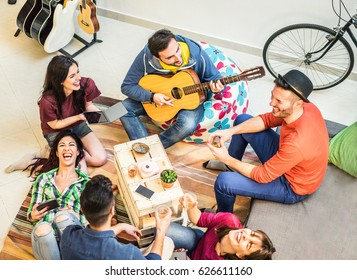 Trendy friends having fun in home living room - Happy young people enjoying time together playing music and drinking shots - Friendship and youth concept - Main focus on top left guys - Warm filter