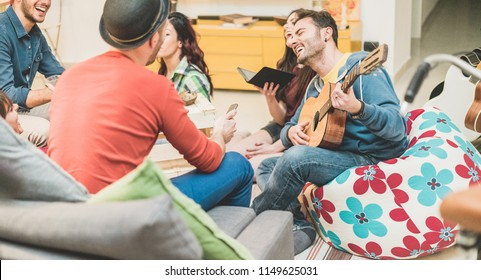 Trendy friends having fun in hostel party living room - Happy millennials people enjoying time together playing karaoke and laughing together - Friendship and youth concept - Focus on right man face