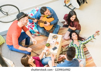 Trendy friends having fun in hostel living room - Happy millennials people enjoying time together playing music and making selfies - Friendship and youth concept - Main focus on top right guys