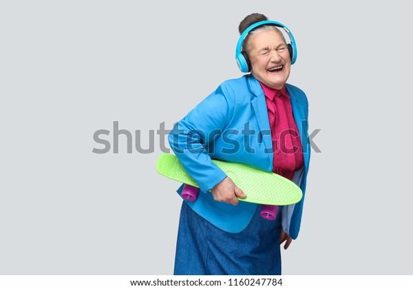 Trendy lustige, lustige Großmutter im bunten, lockeren Stil mit blauen Kopfhörern, die grüne Skateboard halten Musik hören und mit geschlossenen Augen lachen. Indoor-Studioaufnahme einzeln auf grauem Hintergrund.