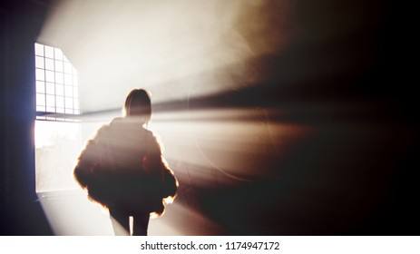 Trendy girl dancing in a fluffy pink coat, blur image. Silhouette on a background of rays of light, dark background
