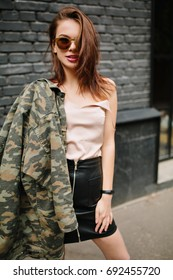 Trendy girl in dark sunglasses holding military jacket on shoulder and confidently posing in front of gray brick background. Outdoor portrait of shapely dark-haired lady in tank-top and leather skirt.