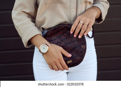 Trendy girl holding small brown leather bag in hand. Stylish accessories