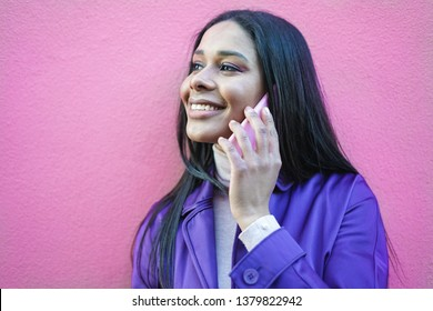 Trendy girl on a pink background, calling her friend and smiling