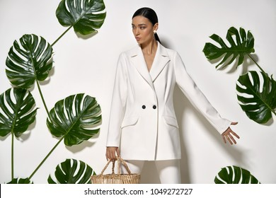 Trendy girl with a straw handbag is posing in a studio on a background of a white wall with big green leaves. She wears a white pantsuit. Woman looks to the side. Horizontal.