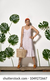 Trendy girl with a straw handbag stands on a wooden platform in a studio on a background of a white wall with big green leaves. She wears a striped pink dress, red headband, bracelets and brown shoes.