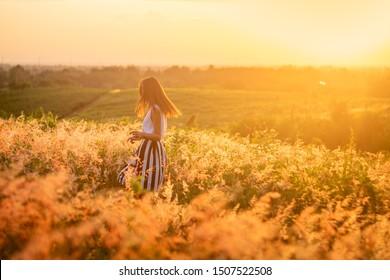 Trendy girl in stylish summer dress feeling free in the field with flowers in sunshine. - Shutterstock ID 1507522508