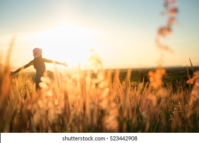 Trendy girl in stylish summer dress with beautiful hat walking in the field with flowers in sunlight